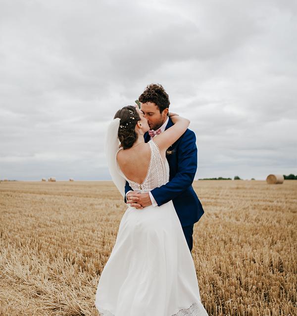 photo de mariage d'un couple qui s'embrasse à la campagne
